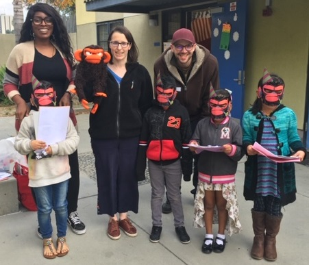 Suzanne and Max Lang with puppet, volunteer, and kids at MacArthur Park Elementary